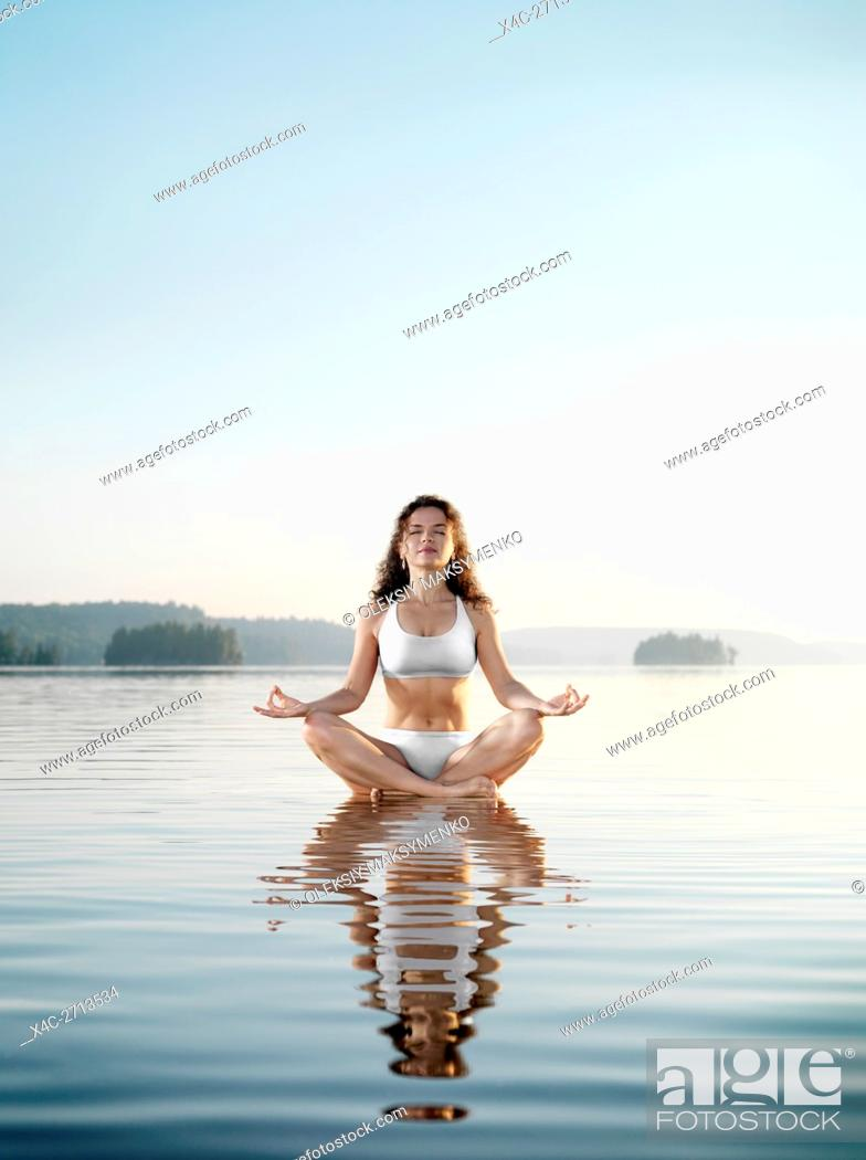 Stock Photo: Young woman in white swimsuit meditating. Practicing meditation on a floating platform in calm water on the lake in early morning during sunrise.