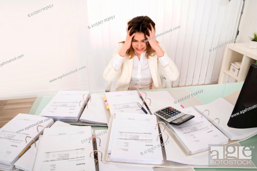 Stock Photo: Frustrated Young Accountant Overloaded With Work In Office.