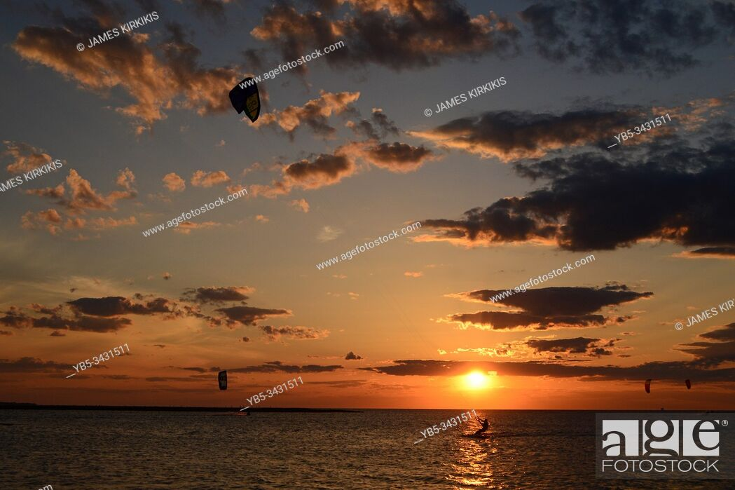 Stock Photo: A kite surfer glides along an almost deserted bay as the sun sets.