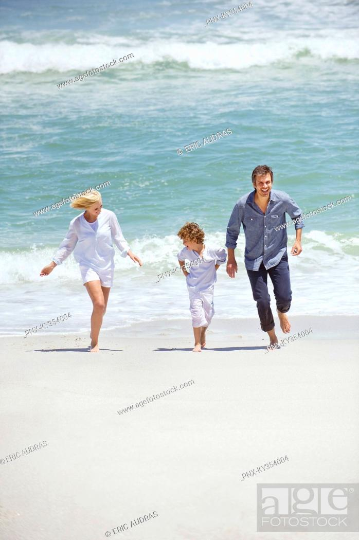 Stock Photo: Couple with their son running on the beach.