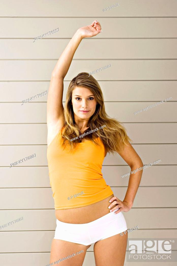 Stock Photo: Portrait of a young woman standing with her hand raised.