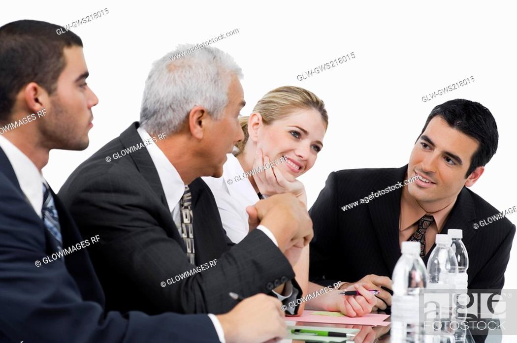 Stock Photo: Three businessmen and a businesswoman at a meeting in a conference room.