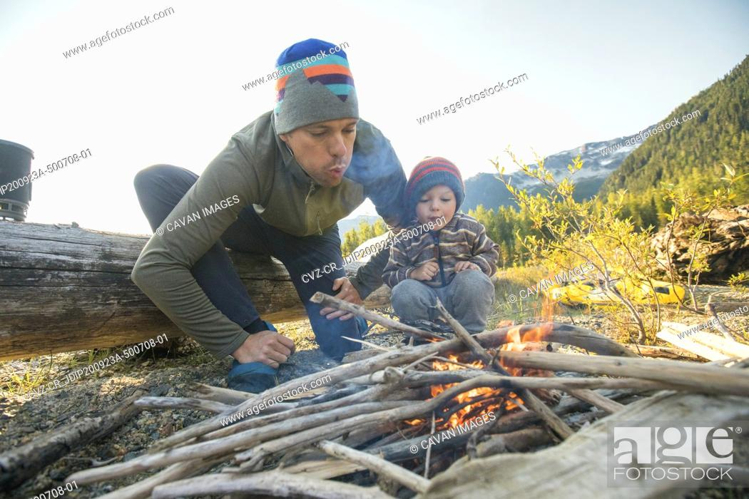 Photo de stock: Father and son work together to start a fire at wilderness campsite.