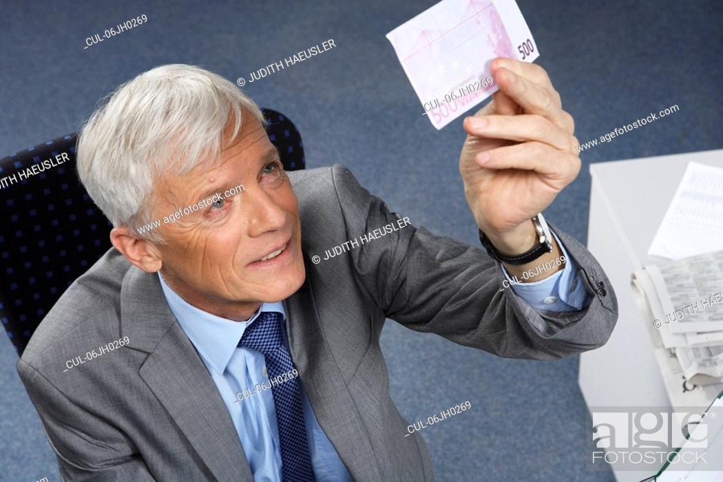 Stock Photo: Businessman checking a 500 euro note.