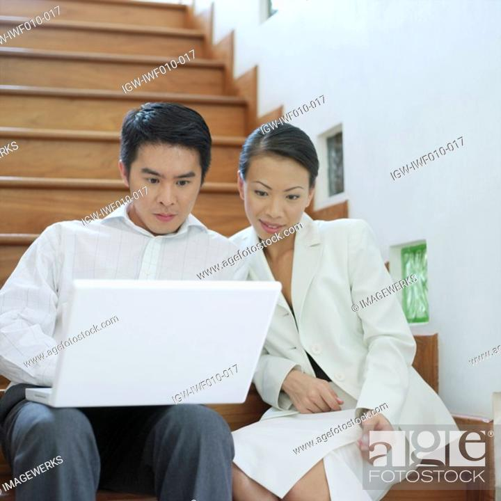Stock Photo: Businessman and businesswoman sitting on a staircase and looking at a laptop.