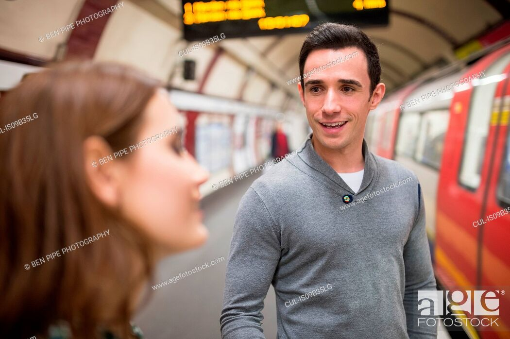 Stock Photo: Man on railway platform talking to friend.