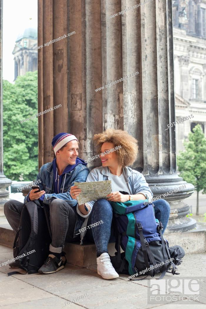 Imagen: Smiling young tourist sitting with map at Altes Museum, Berlin, Germany.