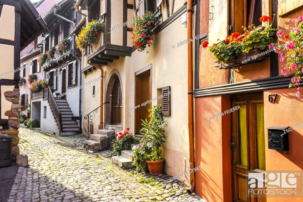 Stock Photo: cobblestone lane in medieval village Eguisheim, Alsace, France, houses behind the town wall.