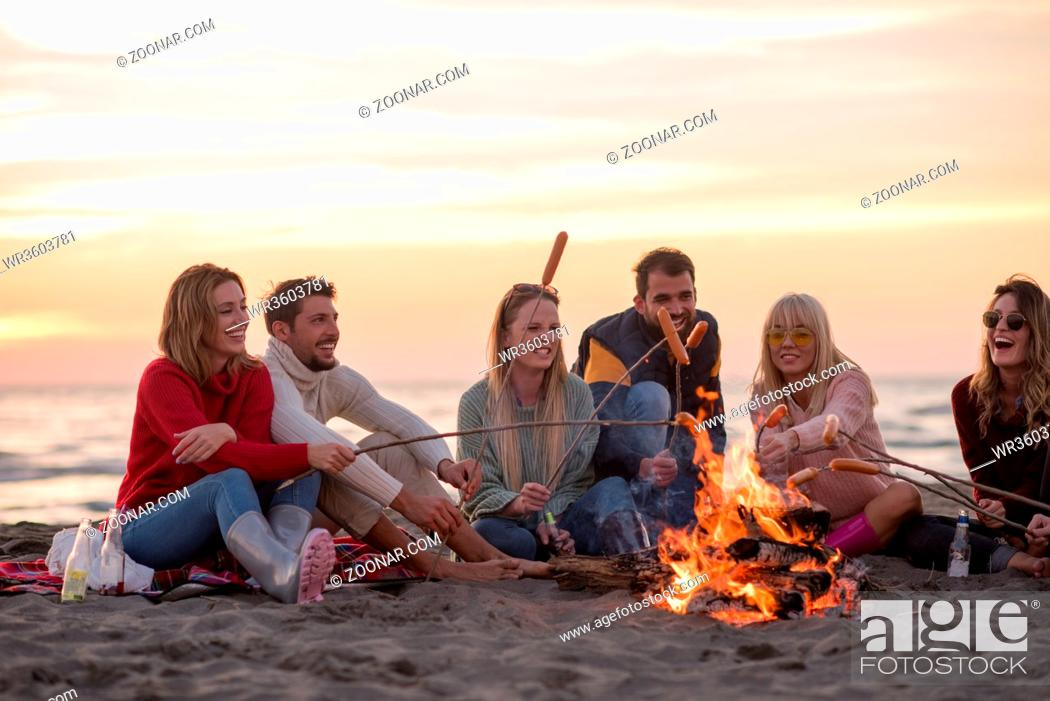 Stock Photo: Group of young friends sitting by the fire at autumn beach, grilling sausages and drinking beer, talking and having fun.
