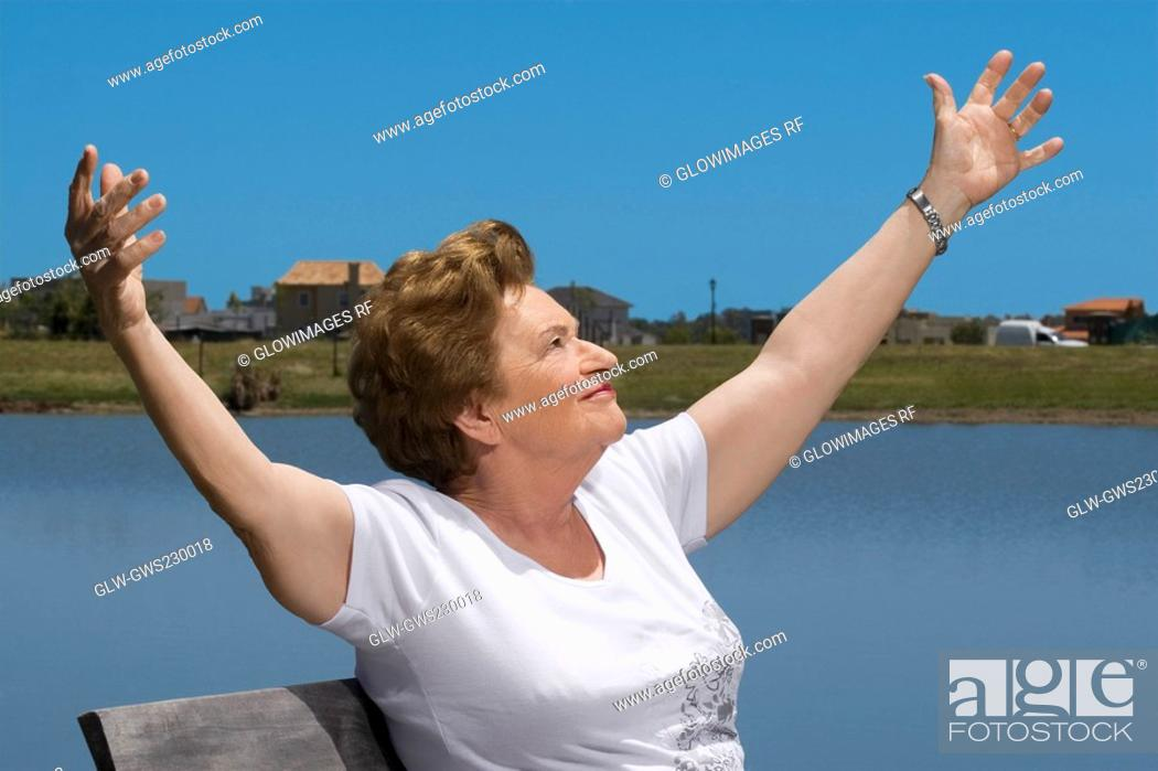 Stock Photo: Senior woman sitting at the lakeside with arms outstretched.