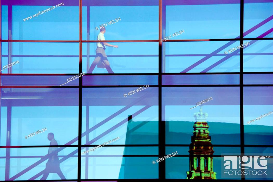 Stock Photo: People crossing glass bridge in Nordea Bank building. Spire of Nikolaj Kirke in background, Copenhagen, Denmark.