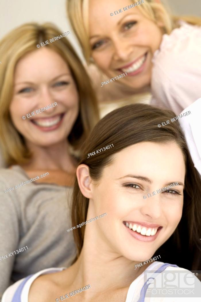 Stock Photo: Three women smiling for the camera, indoors.