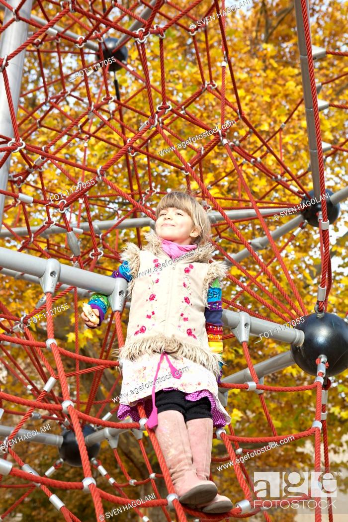 Stock Photo: Girl standing on jungle gym.