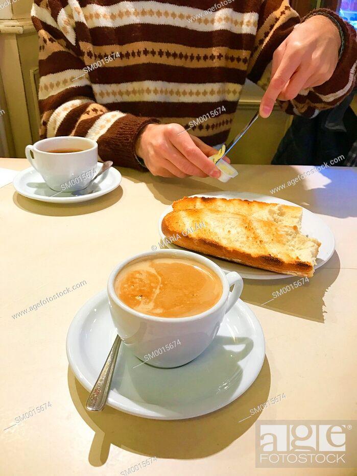 Stock Photo: Man spreading butter on toast at breakfast.