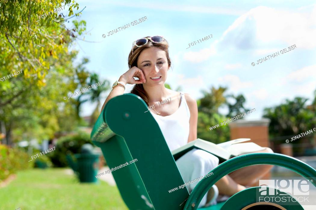 Stock Photo: A woman relaxing on a park bench with a book.