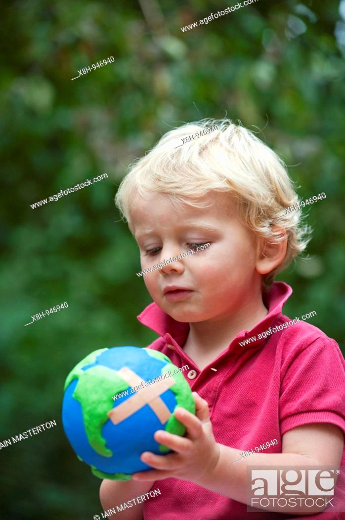 Stock Photo: young boy holding a model of a sick planet Earth with a band-aid stuck on it.