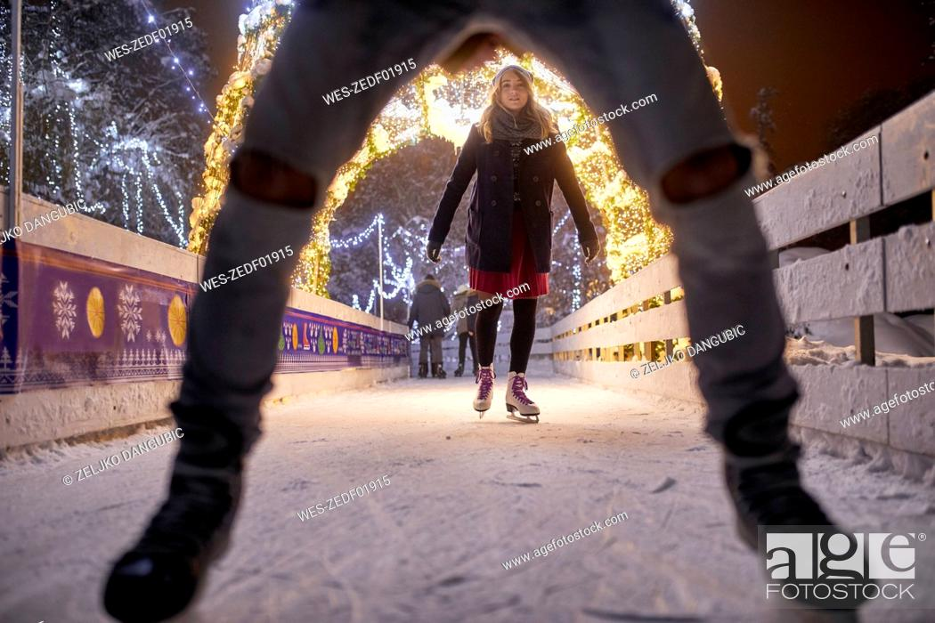 Stock Photo: Young woman ice skating on an ice rink at night.