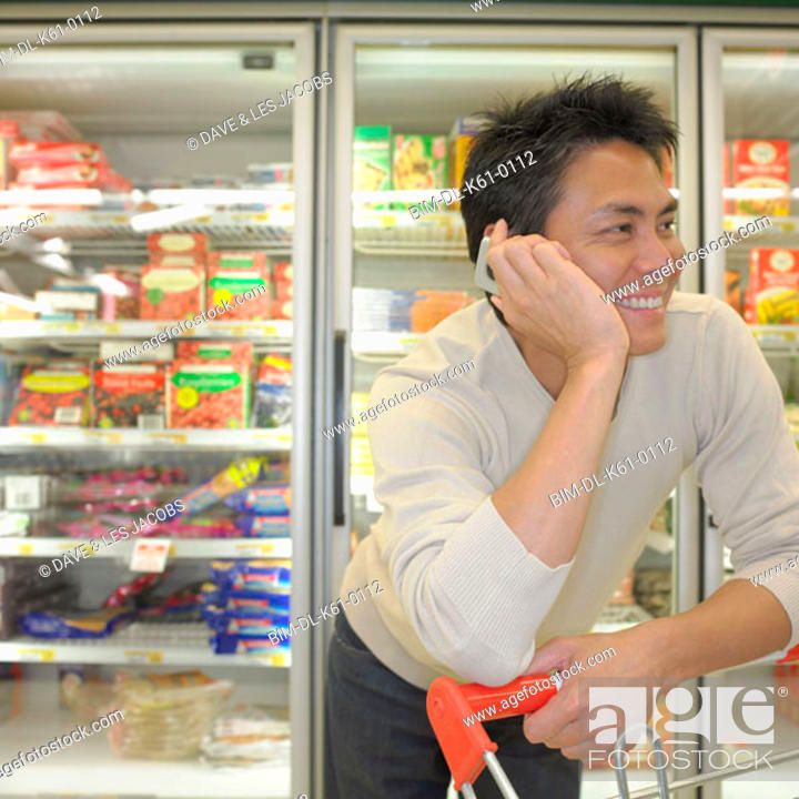 Stock Photo: Asian man on cell phone at supermarket, Perth, Australia.