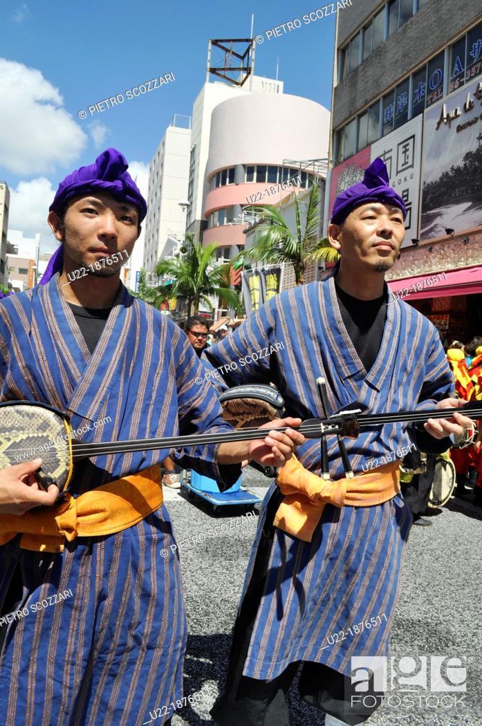Stock Photo: Naha, Okinawa, Japan, men in traditional Okinawan outfit, playing Sanshin, at the 10 000 Taiko Eisa dance parade along Kokusai-dori, August.