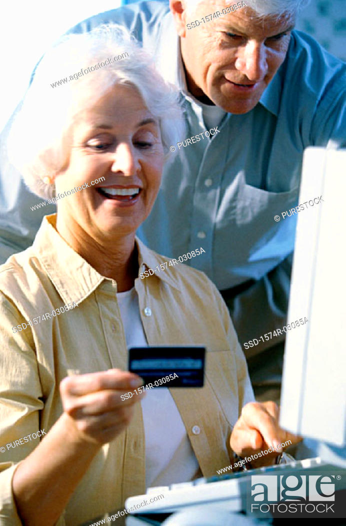 Stock Photo: Senior couple in front of a computer holding a credit card.