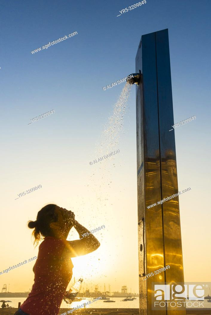 Stock Photo: Las Palmas, Gran Canaria, Canary Islands, Spain. A female jogger at sunrise cooling down under a beach shower following morning run on the city beach in Las.