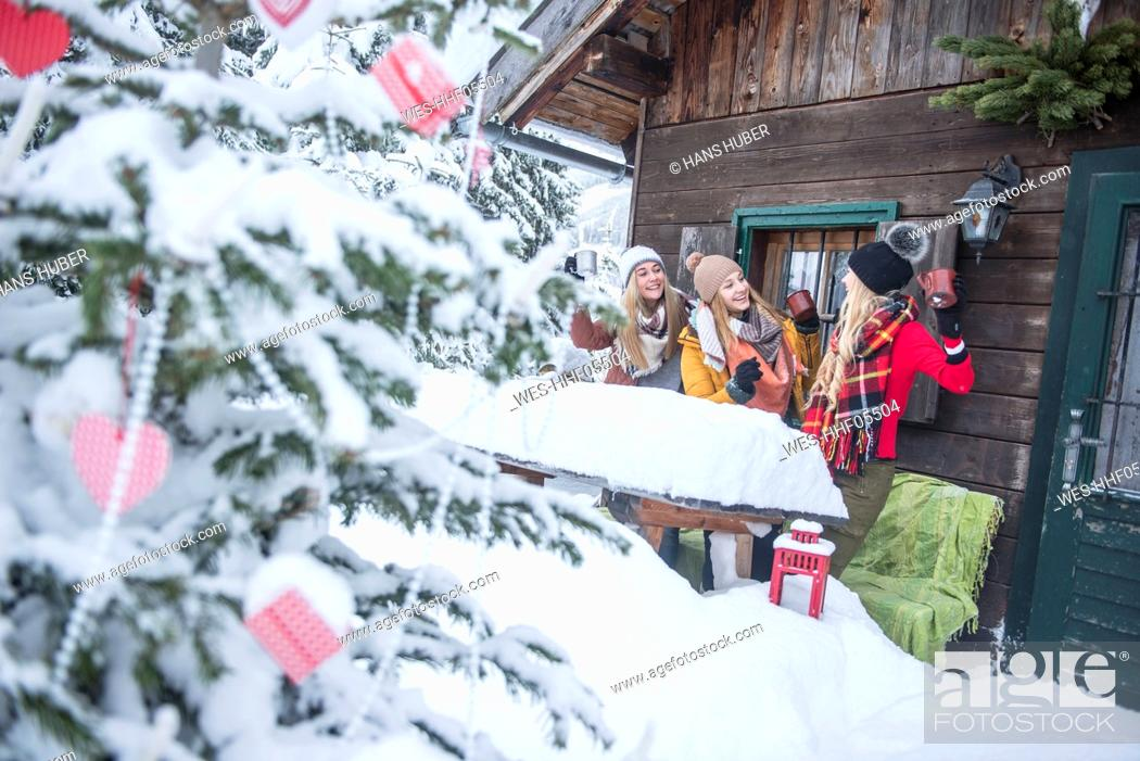 Stock Photo: Austria, Altenmarkt-Zauchensee, female friends celebrating at wooden house at Christmas time.