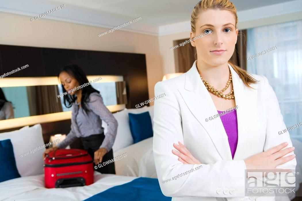 Stock Photo: Portrait of a businesswoman standing with her arms crossed with another businesswoman packing her luggage.