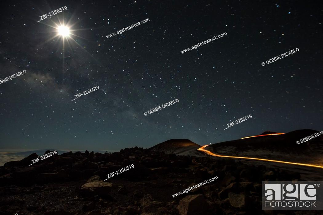 Imagen: The Milky Way and Moon from the summit of Haleakala, Hawaii. Car tail lights and headlights snake further up the summit to the observatory.