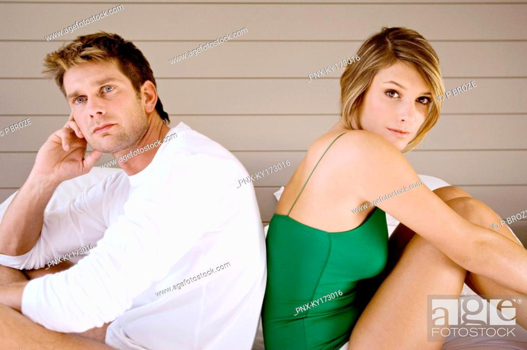 Stock Photo: Side profile of a mid adult man and a young woman sitting back to back on the bed.