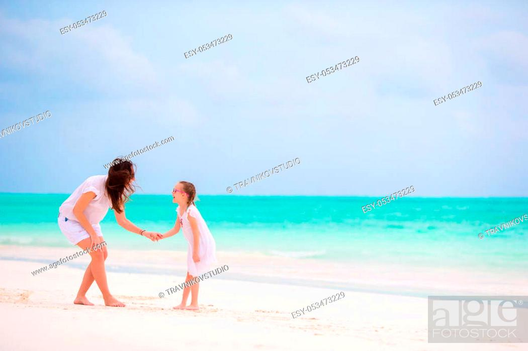 Stock Photo: Beautiful mother and her adorable little daughter at beach.