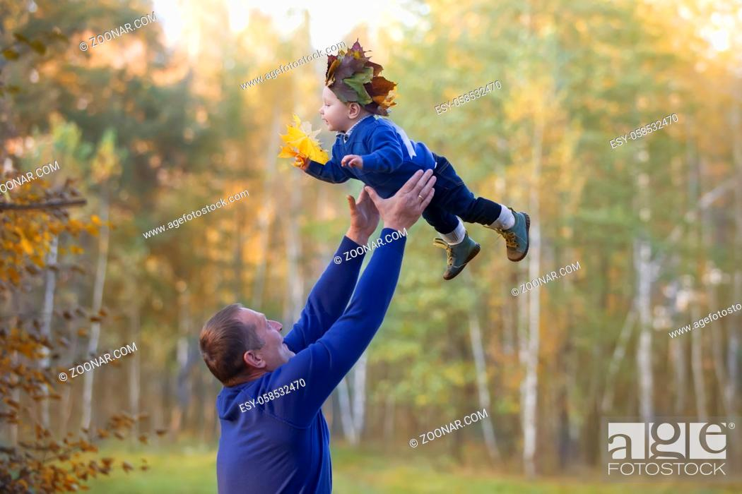 Photo de stock: Dad throws up a little son on an autumn walk.Parent with baby.