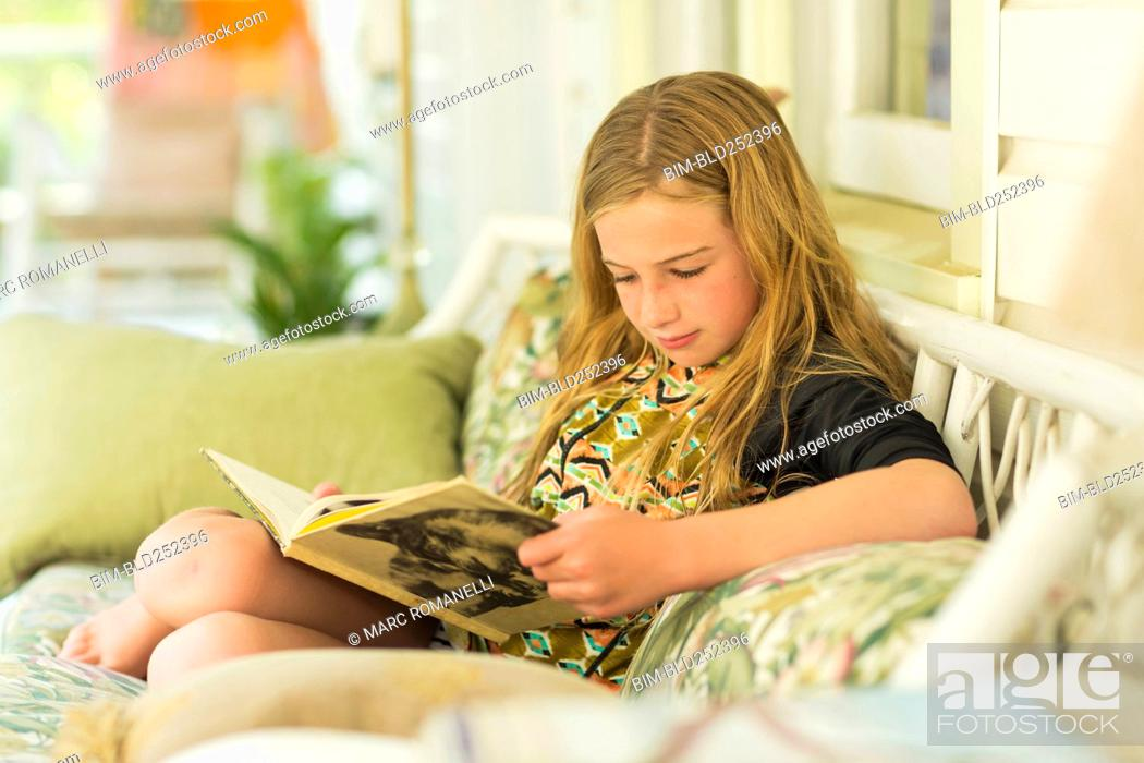 Stock Photo: Caucasian girl reading book on sofa.