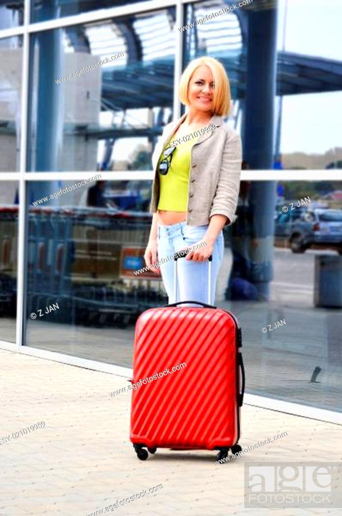 Stock Photo: Young woman with luggage at the airport. Traveling tourist.