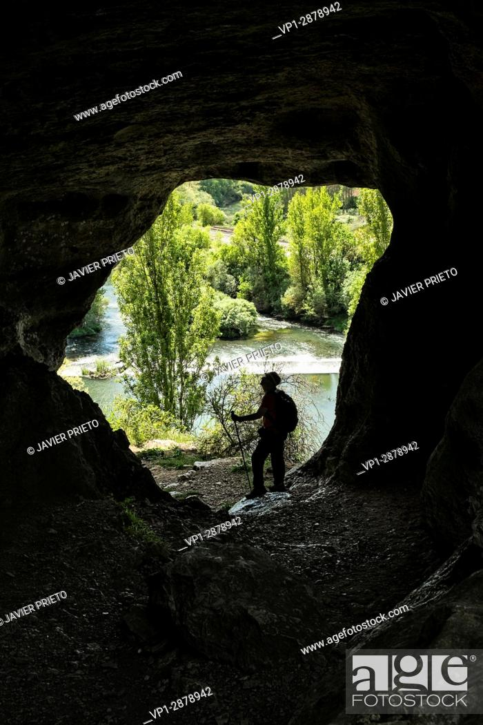 Stock Photo: A walker stopped in the natural tunnel of access to the top of the canyon of La Horadada, with the river Pisuerga in the background.