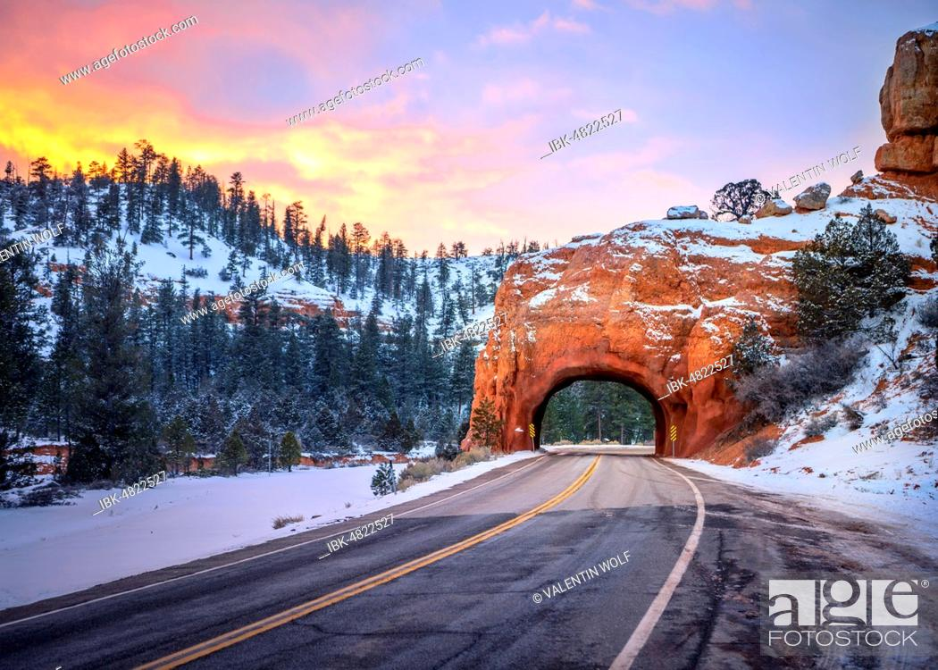Stock Photo: Road with tunnel through red rock arch in snow, at sunset, Highway 12, sandstone rocks, Red Canyon, Panguitch, Utah, USA.