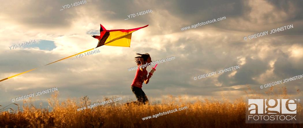 Stock Photo: A panorama of a girl happily flying her kite.