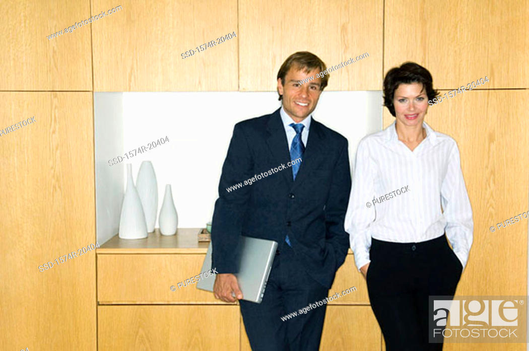 Stock Photo: Portrait of a businessman standing with a businesswoman and smiling.
