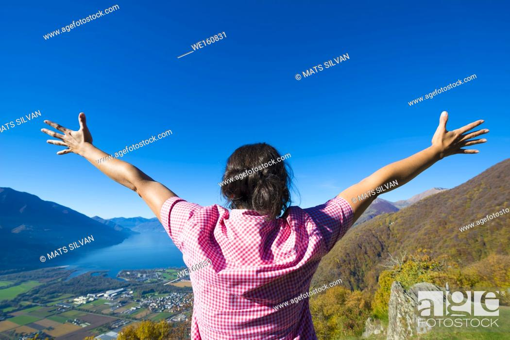 Stock Photo: Rear View of Woman with Arms Outstretched on Mountain with Alpine Lake Maggiore in Ticino, Switzerland.