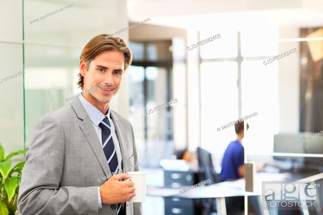 Stock Photo: Portrait of smiling businessman with coffee cup.