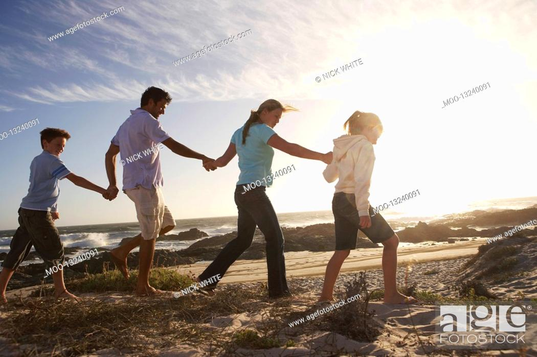 Stock Photo: Parents and children walking hand in hand on seashore side view.