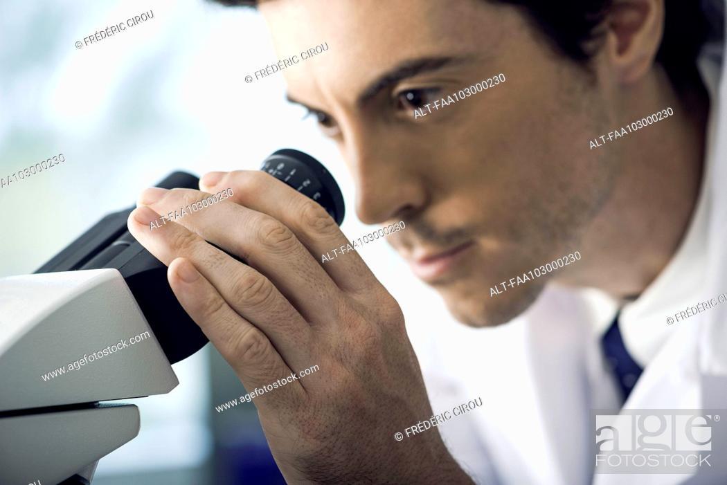 Imagen: Scientist analyzing specimen under microscope.