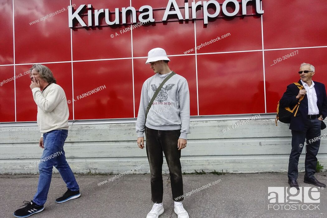 Stock Photo: A teenage boy stands at the arrivals area at the Kiruna aiport. Kiruna, Sweden.
