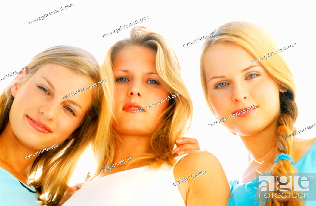 Stock Photo: Low angle view of three young women looking down.