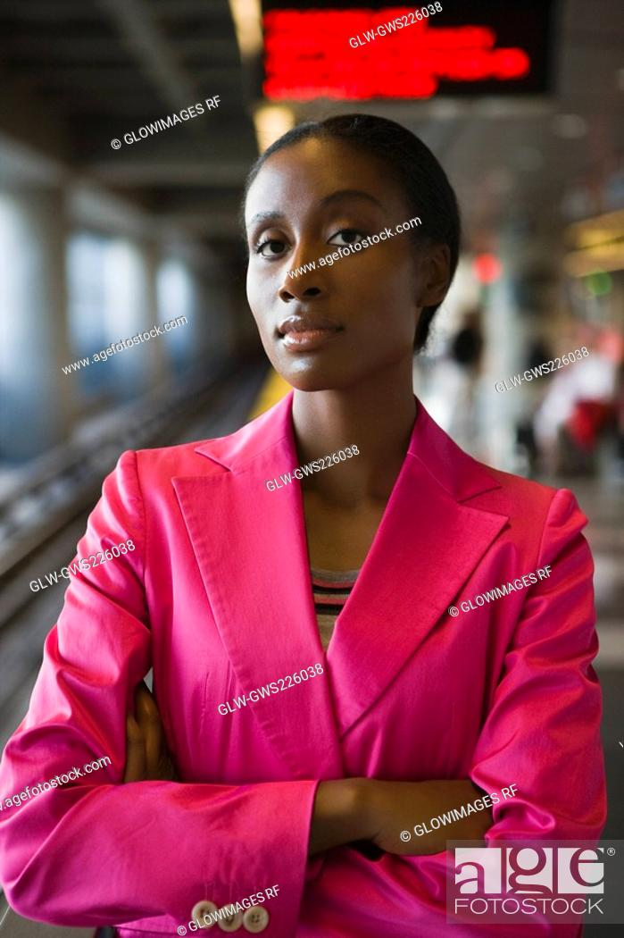 Stock Photo: Portrait of a businesswoman standing with her arms crossed at a subway station.