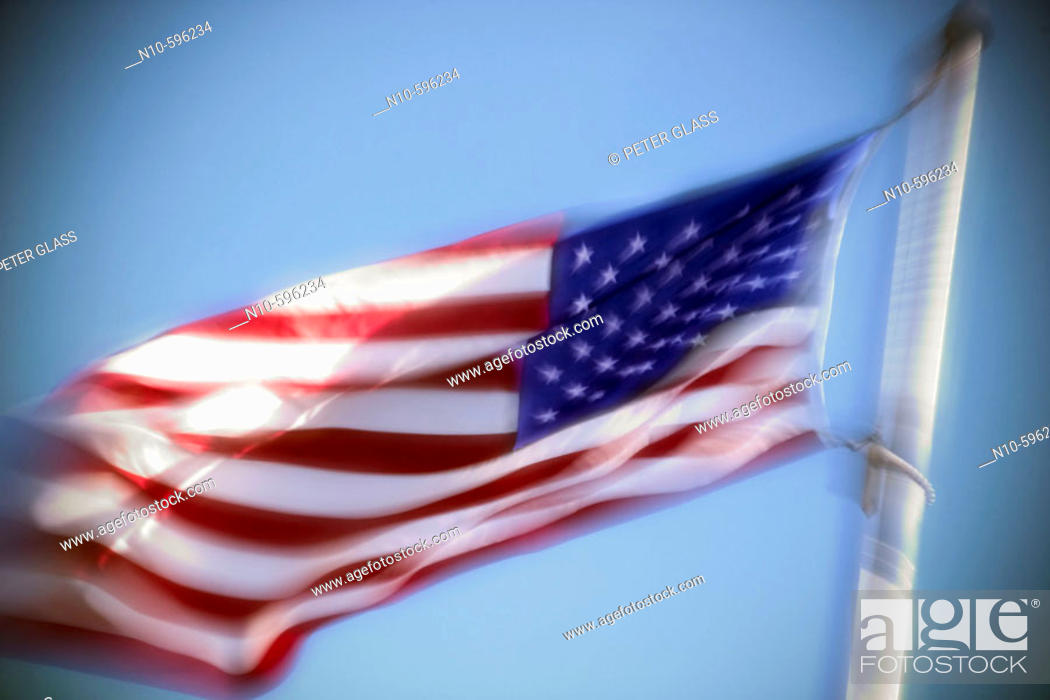 Stock Photo: An American flag billowing in the wind against a blue sky.