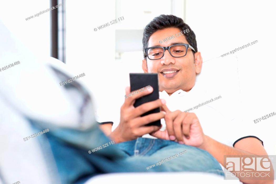 Stock Photo: Smartphone social media concept. Indian guy using mobile phone. Asian man relaxed and lying on sofa indoor. Handsome male model.