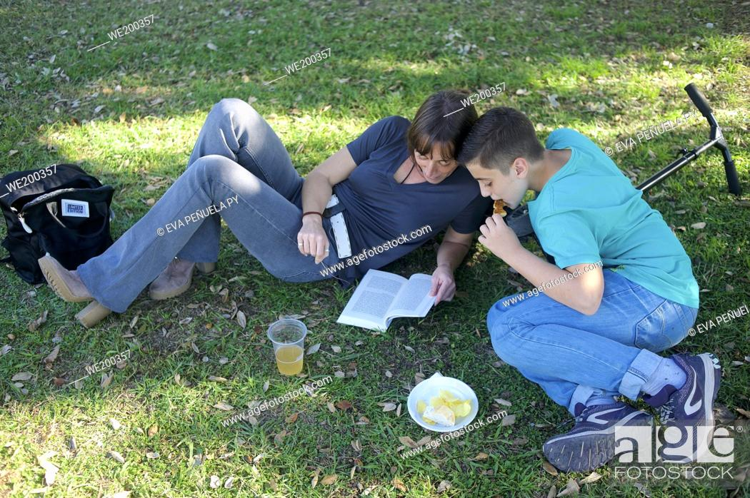 Photo de stock: Mother and son having a picnic on the grass.