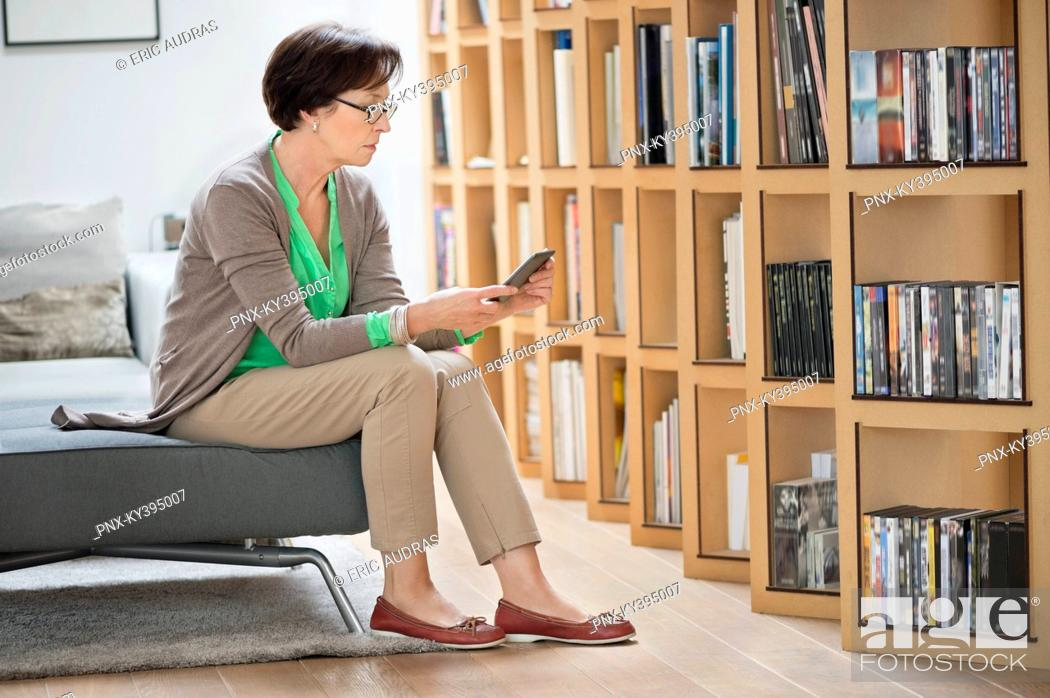 Stock Photo: Woman sitting on a couch and reading a book.