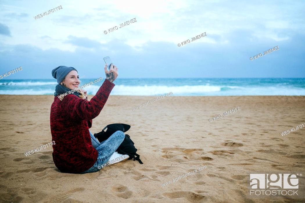 Stock Photo: Smiling young woman sitting on the beach in winter using cell phone.