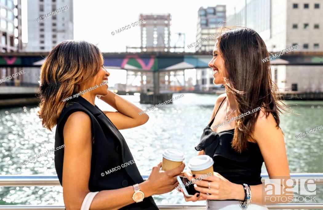Stock Photo: Two women having a coffee break on a bridge in the city.